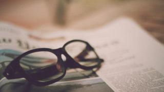 黒ぶち眼鏡と英字新聞